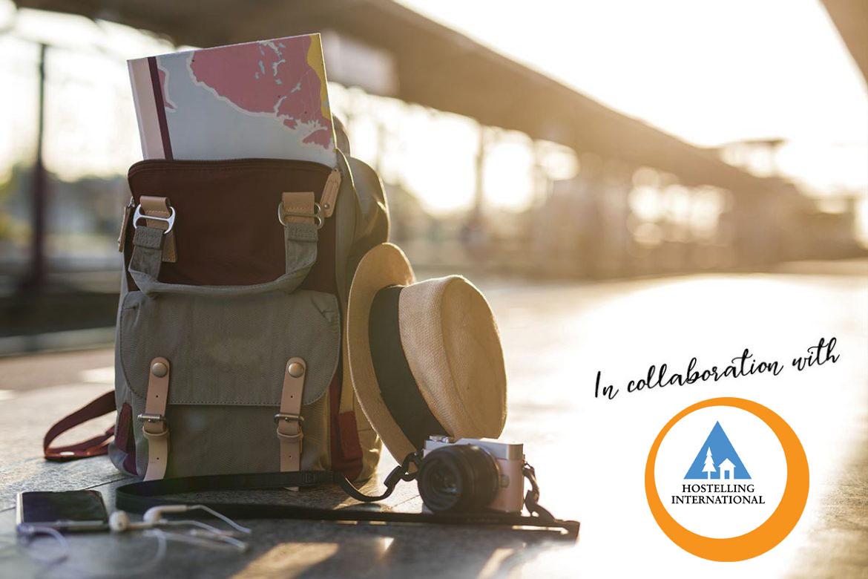 Rucksack, Weltkarten, Fotoapparat und Hut vor einer Brücke