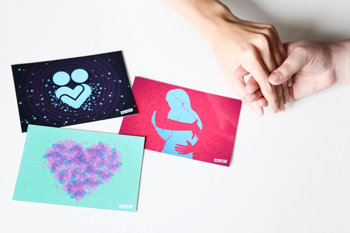 Flatlay mit Postkarten aus der AllOut Aktion und Händen, die sich halten