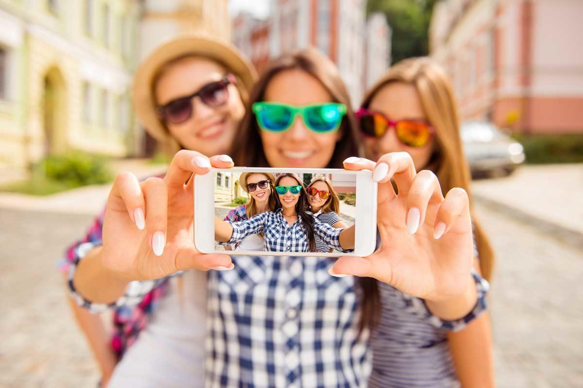 Drei Frauen in Sonnenbrillen machen ein Selfie mit einem Handy