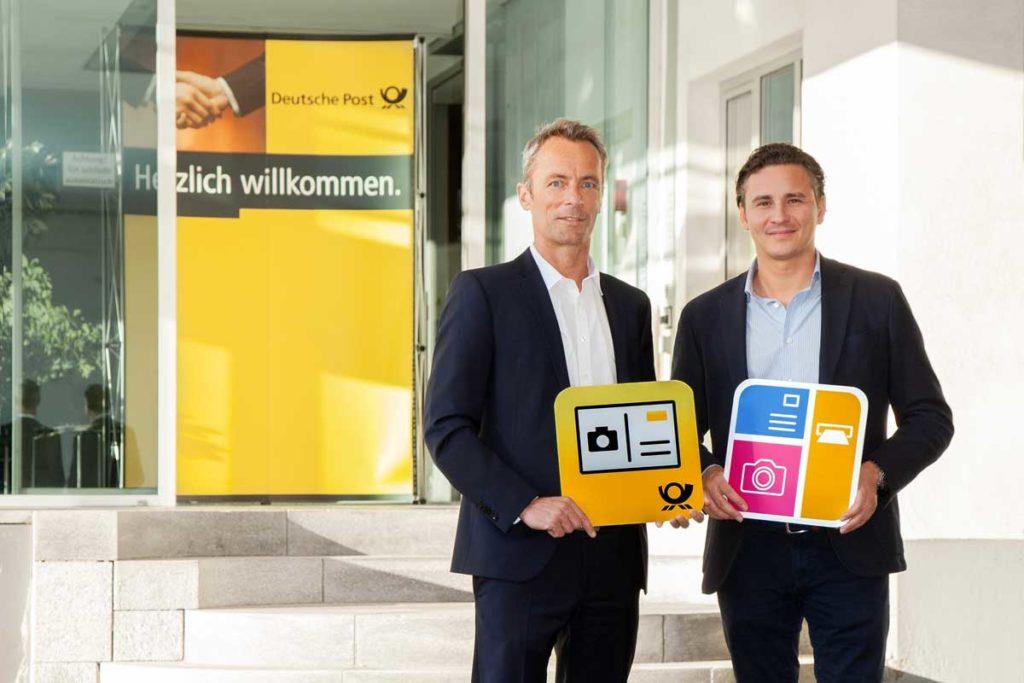 Oliver Kray (MyPostcard) und Kai Schmude (Deutsche Post) halten Icons