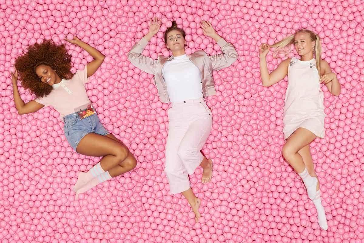 Drei Mädchen liegen im Meer aus pinken Bällen