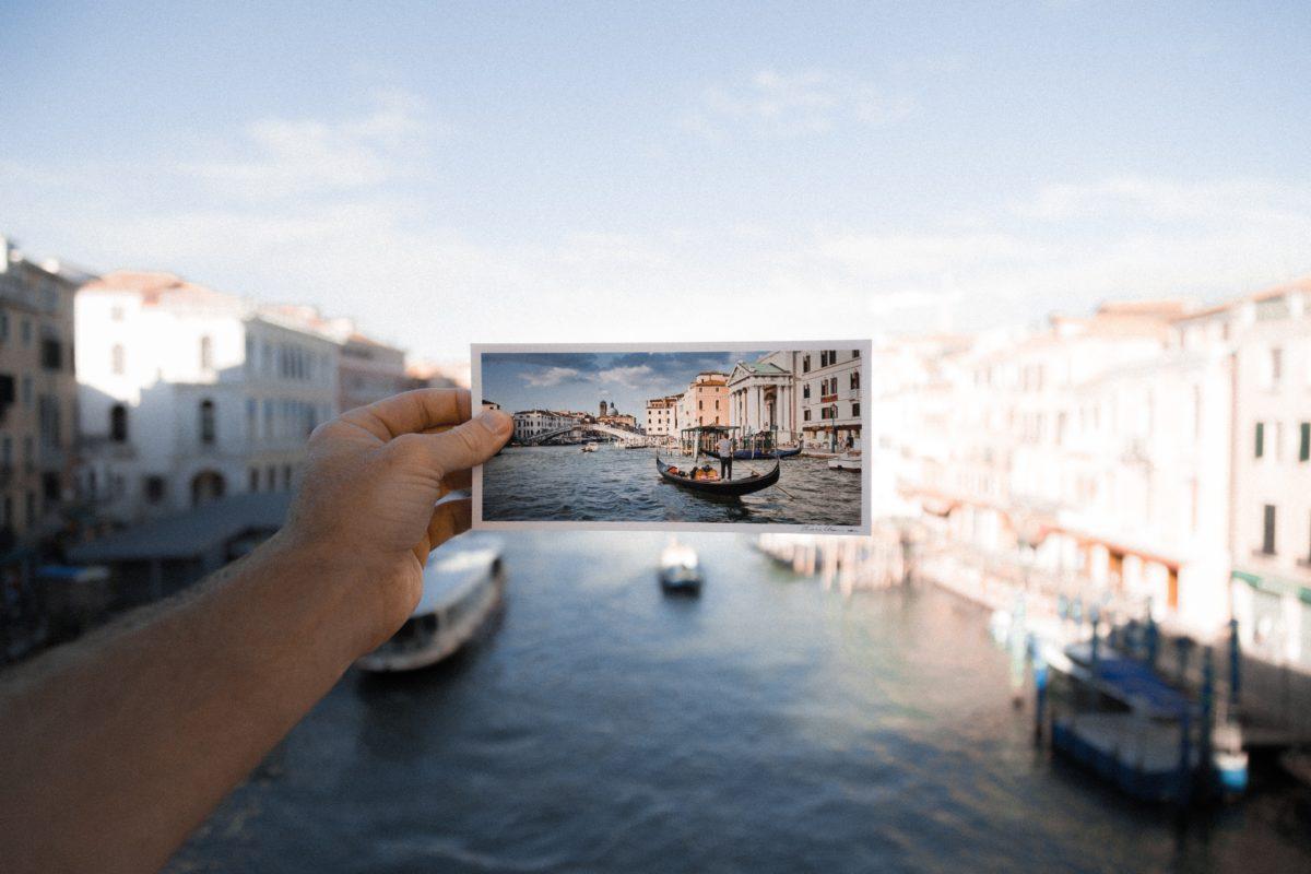 Hand mit Postkarte, Motiv Postkarte und Kulisse identisch